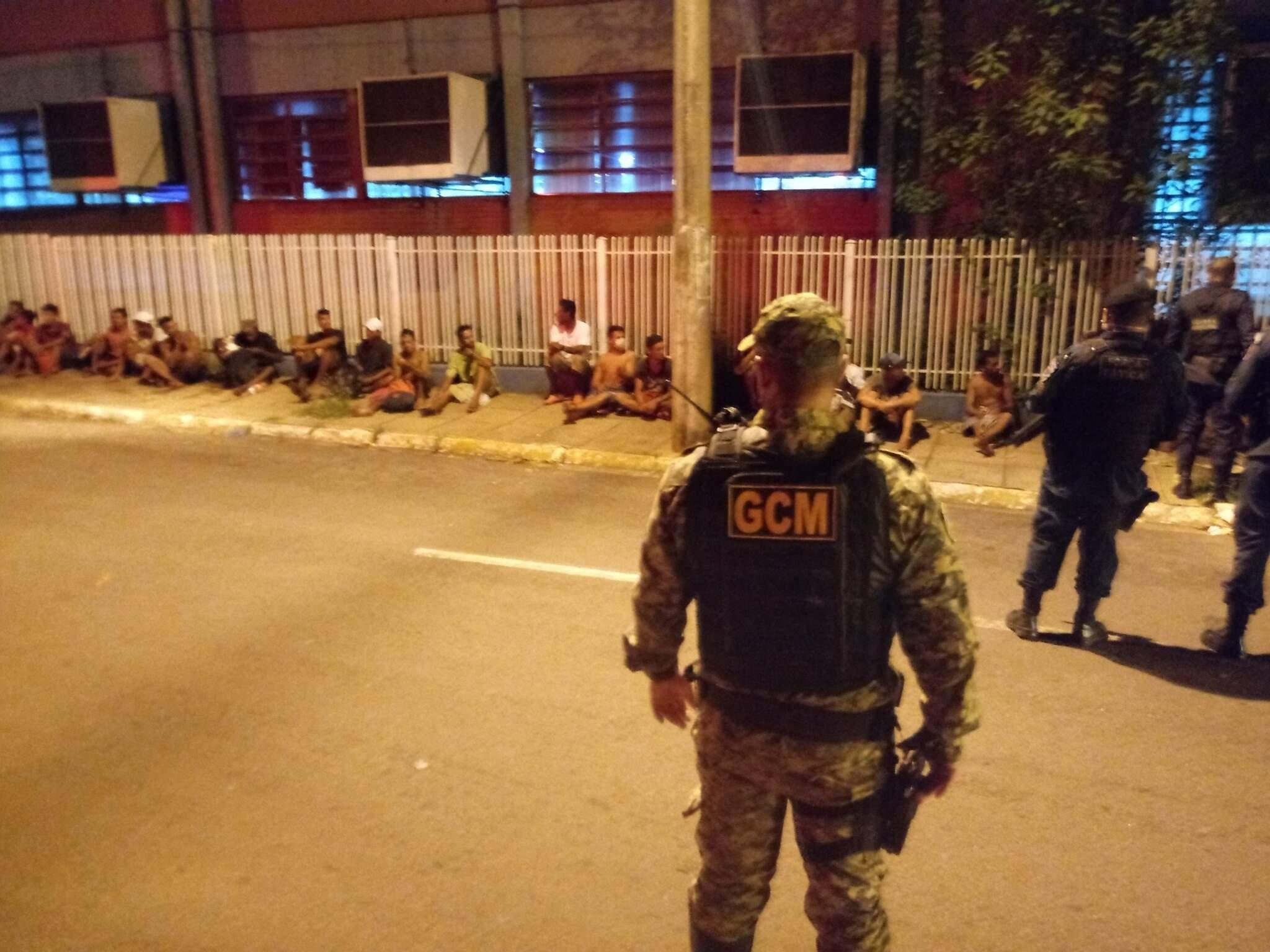Sentados na calçada, moradores de rua são observados por guardas civis municipais. (Foto: Divulgação)