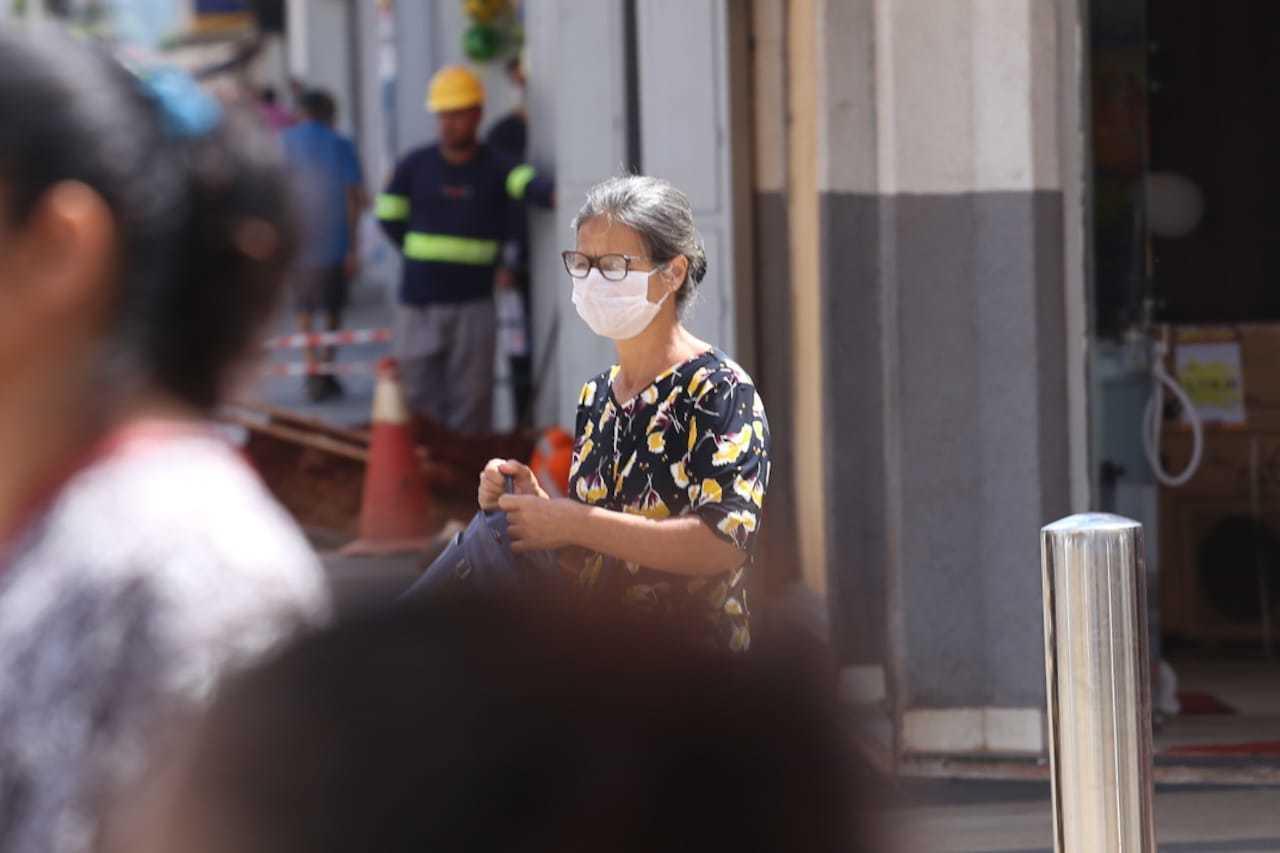 Receosa com o contágio da doença, moradora usa máscara de proteção em pleno Centro da cidade. (Foto: Marcos Maluf)