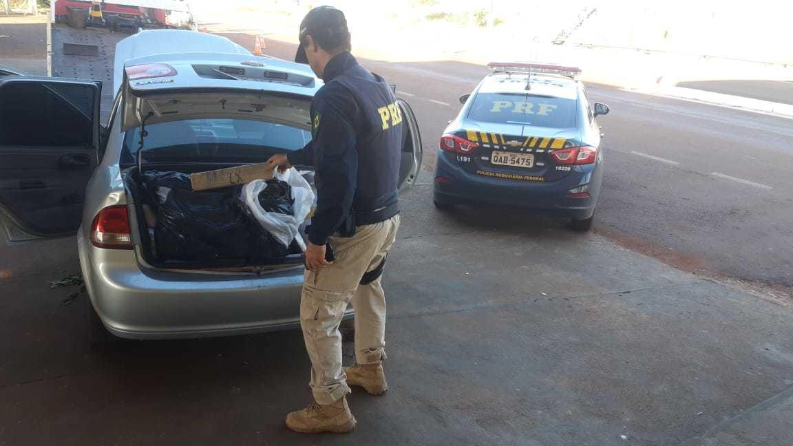 Policia retirando os tabletes da droga do porta-malas do veículo. (Foto: Divulgação/PRF)