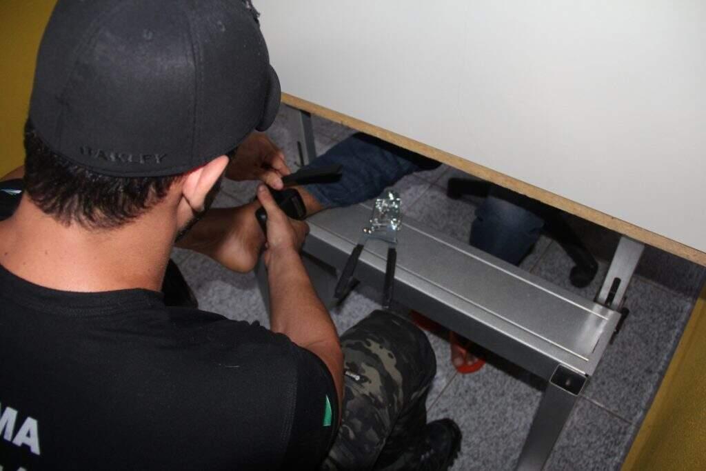 Agente instalando a tornozeleira eletrônica em detento. (Foto: Tatyane Santinoni)
