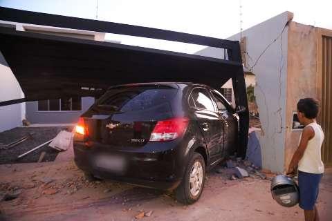 Carro é atingido durante ultrapassagem e derruba muro de residências
