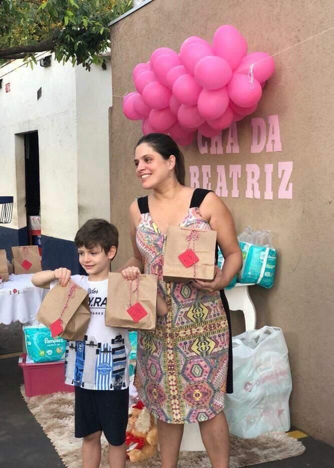 Priscila e o filho, Renan, segurando as sacolinhas com as guloseimas da comemoração. (Foto: Arquivo pessoal)