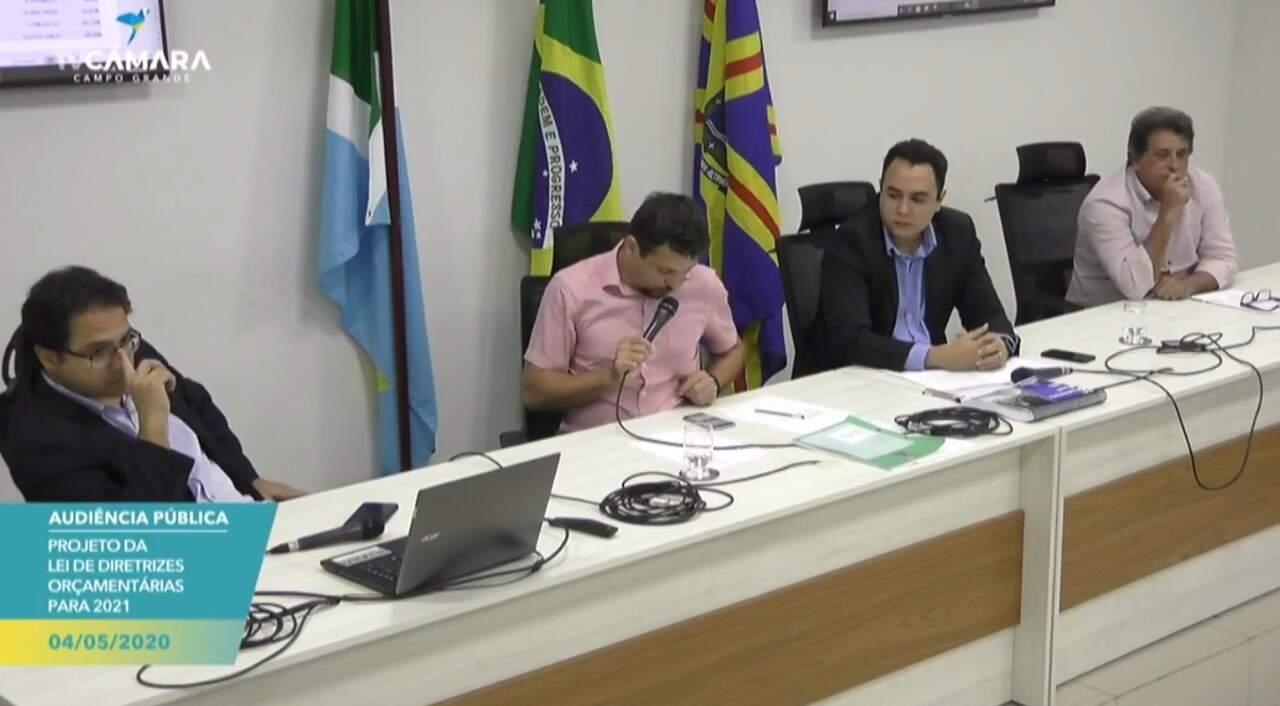 Audiência pública com o secretário Pedro Pedrossian Neto, ao lados dos vereadores Eduardo Romero (Rede), Odilon de Oliveira (PSD) e Ademir Santana (PSDB), na Câmara Municipal (Foto: Reprodução)
