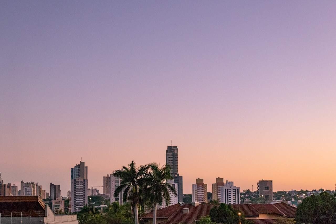 Edifício, árvores e coqueiros compõem cenário do dia amanhecendo no Bairro Itanhanguá Park, na Cidade Morena (Foto: Henrique Kawaminami)