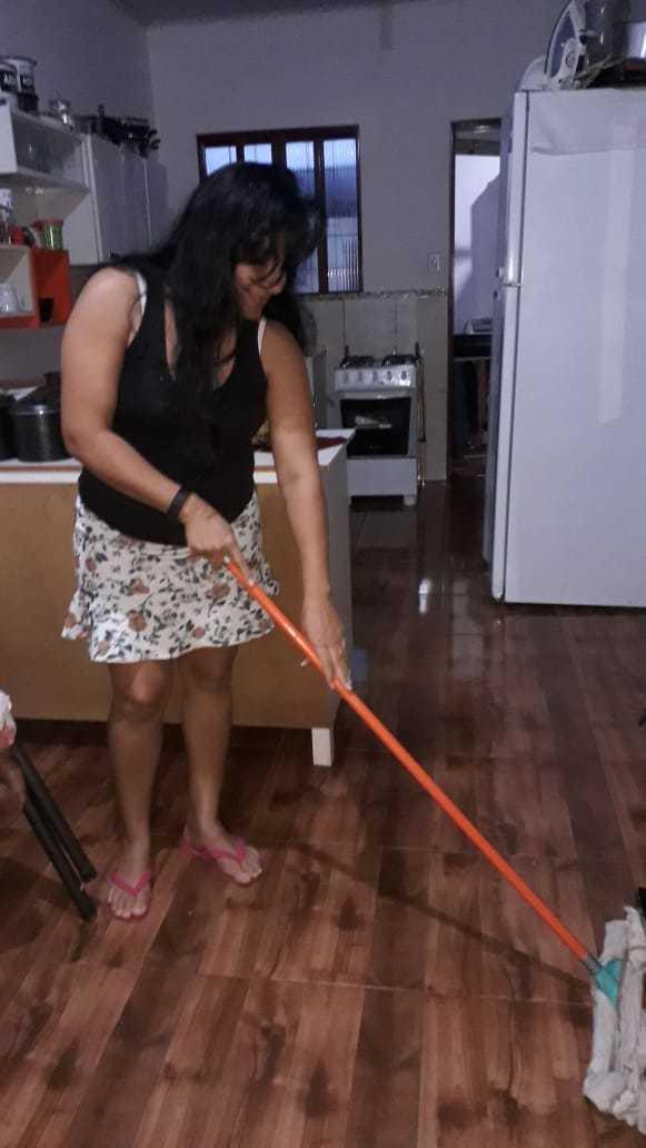 Paula Esquivel passando pano no chão da casa onde mora. (Foto: Arquivo pessoal)