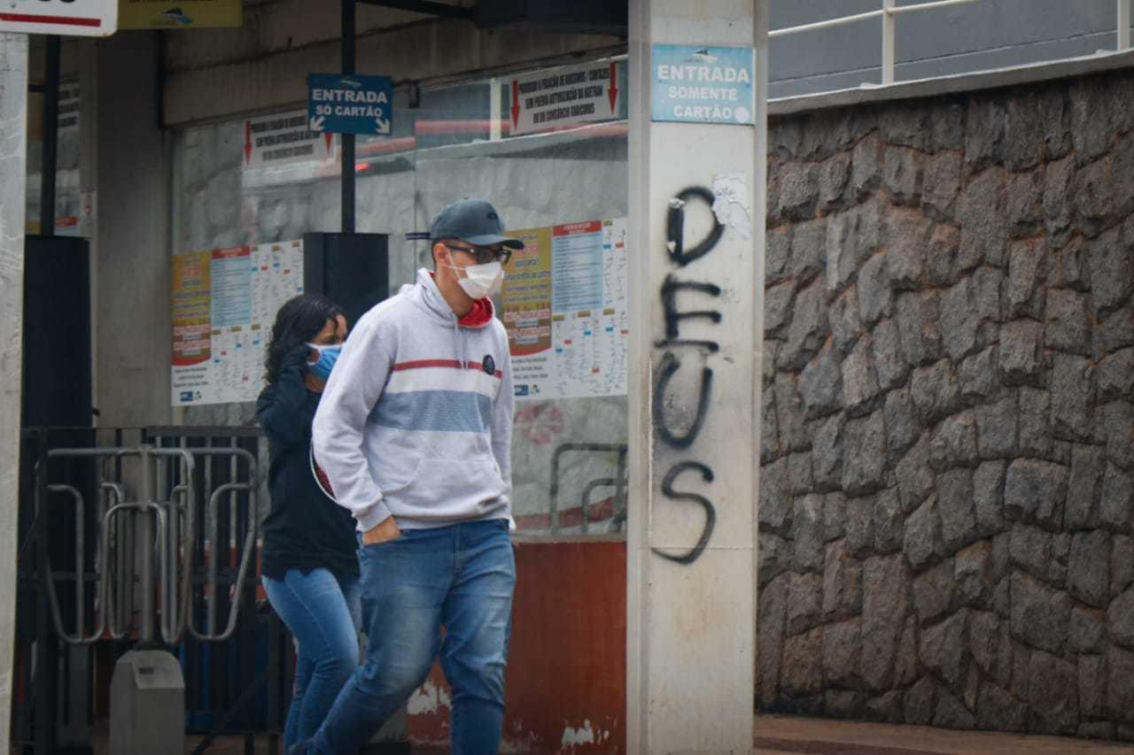 Pedestre se protegendo contra o vírus usando máscara enquanto anda por rua da Capital. (Foto: Henrique Kawaminami)
