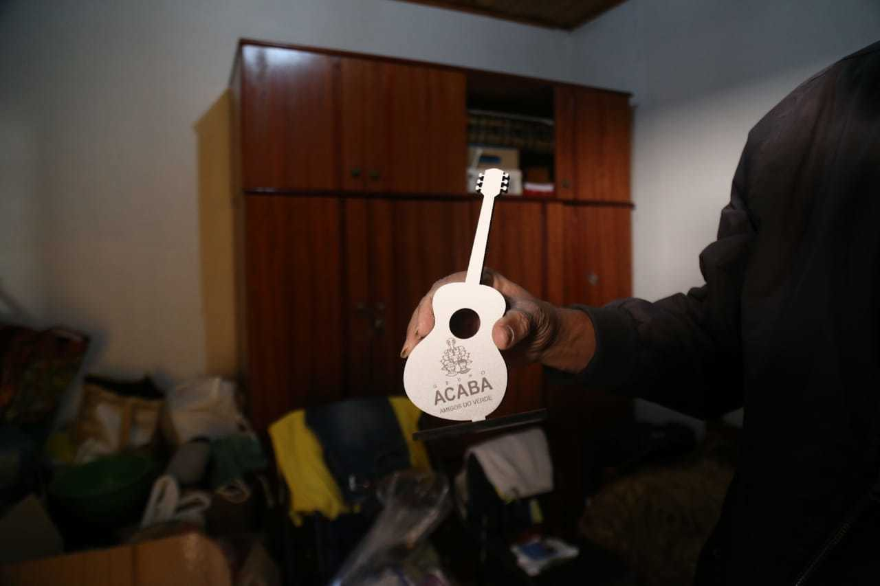 Vandir segurando um violão pequeno de enfeite com o nome do Grupo Acaba. (Foto: Marcos Maluf)