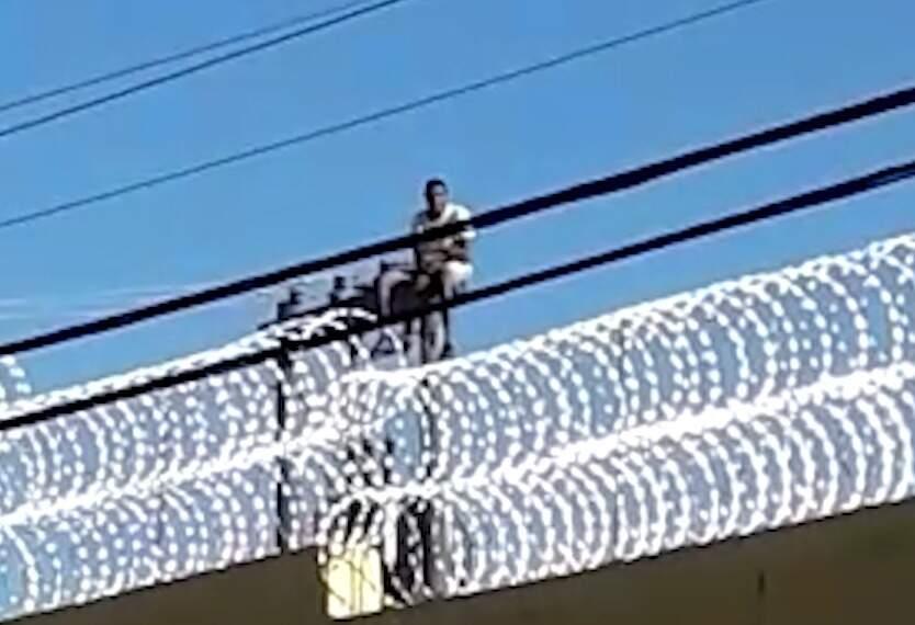 Presidiário ficou preso na rede de energia e não cosegue descer (Foto: reprodução/vídeo)
