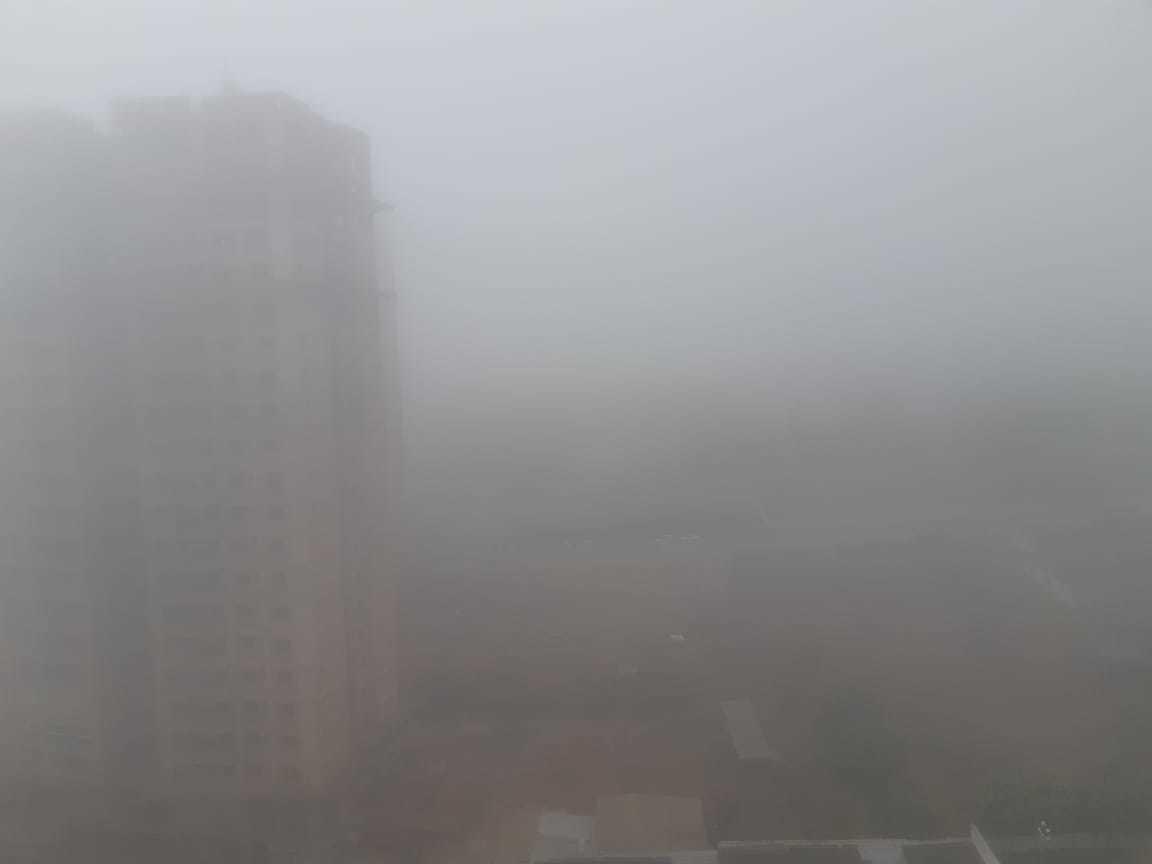 Prédio encoberto pela neblina na região central de Campo Grande; frente fria não deixa máxima passar dos 22°C hoje, na cidade (Foto: Anahi Zurutuza)