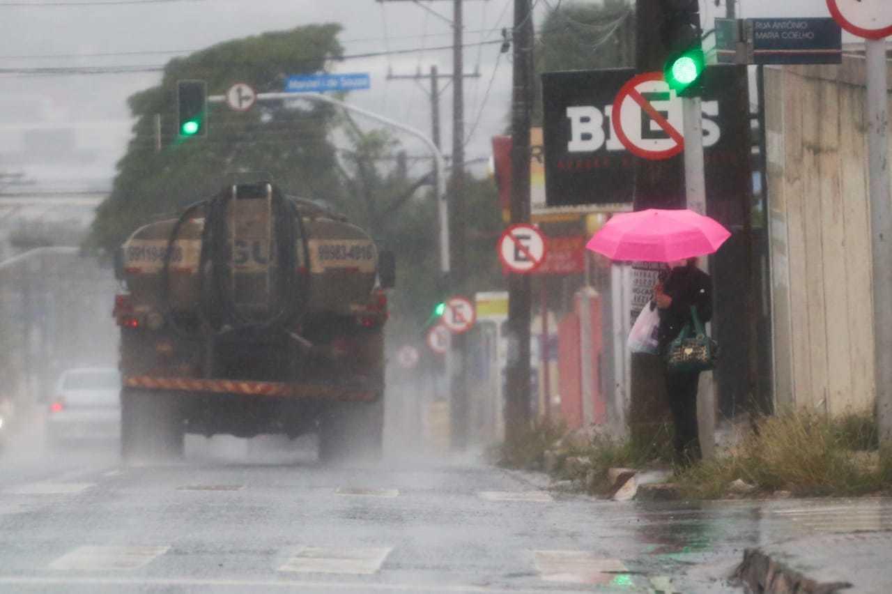 Mulher se protege da chuva e aguarda sinal fechar (Foto: Marcos Maluf)