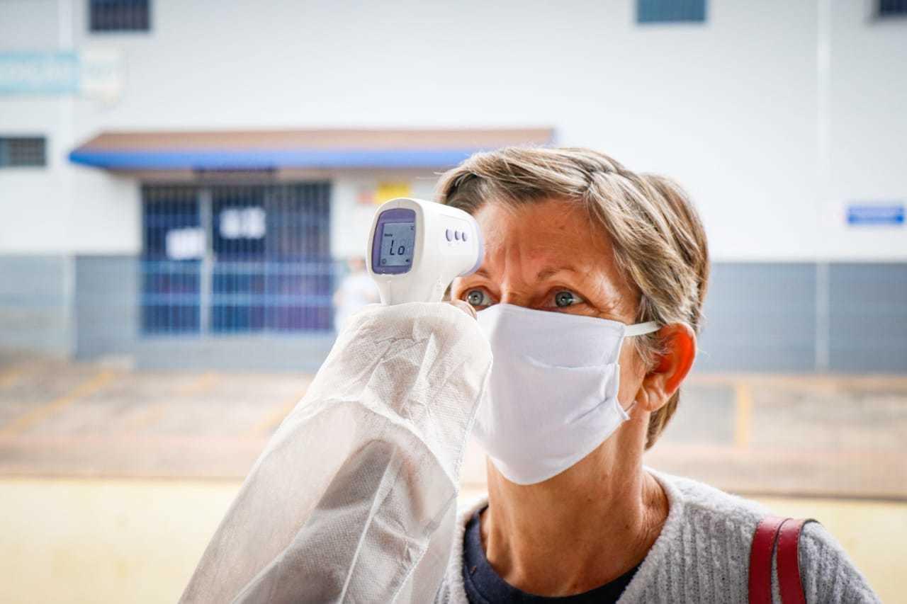 Mulher passa por aferição de temperatura na Capital (Foto: Henrique Kawaminami)