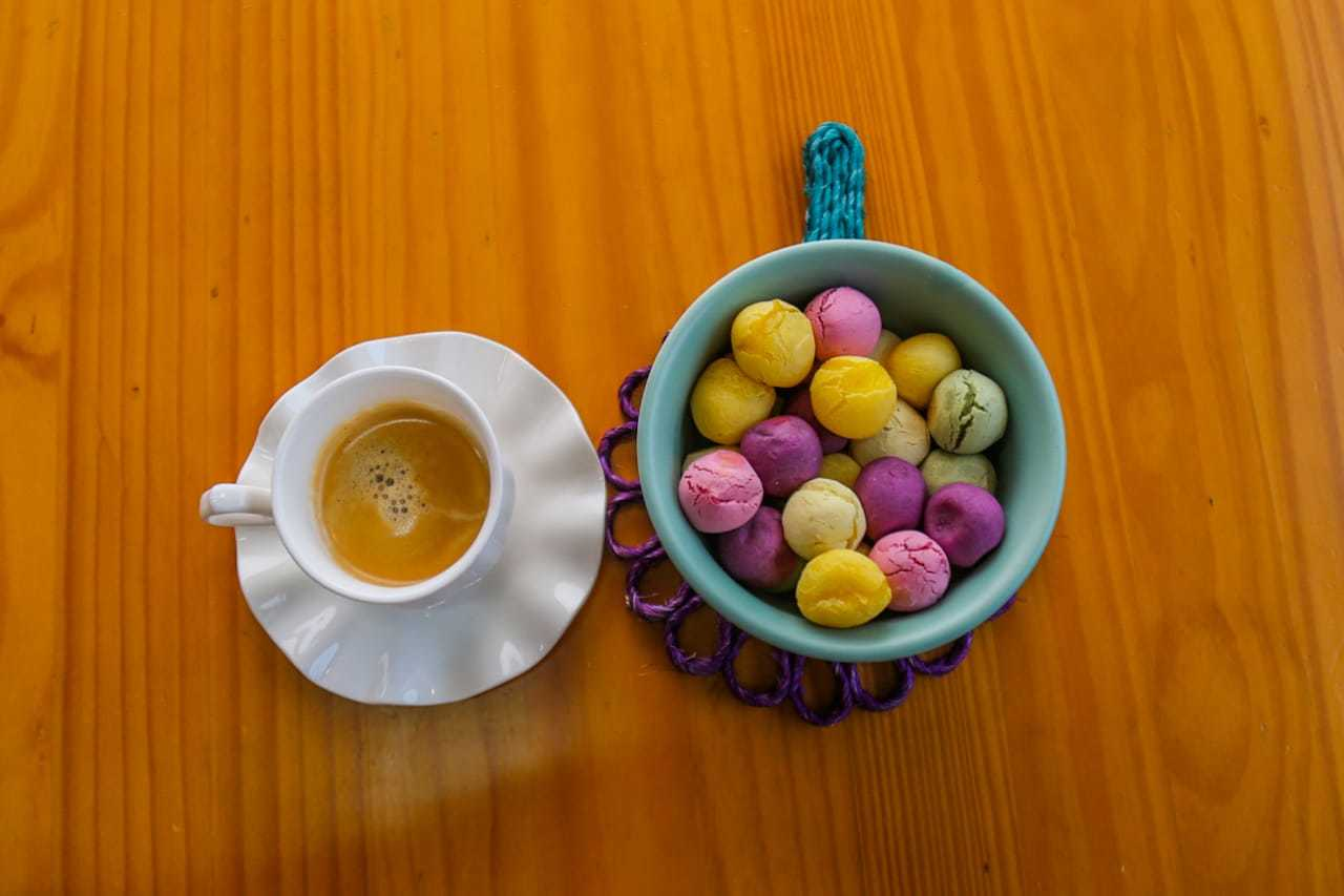 Uma xícara de leite com café ao lado dos pãezinhos coloridos feitos de legumes. (Foto: Marcos Maluf)