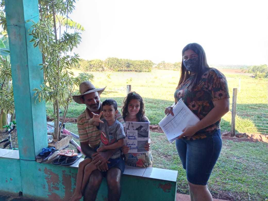A professora Ana Cecília entregando atividade para a aluna Eduarda Rezende da Silva e sua família numa fazenda que fica na região da Escola Municipal Oito de Dezembro (Foto: Alcemir Martins Corrêa)