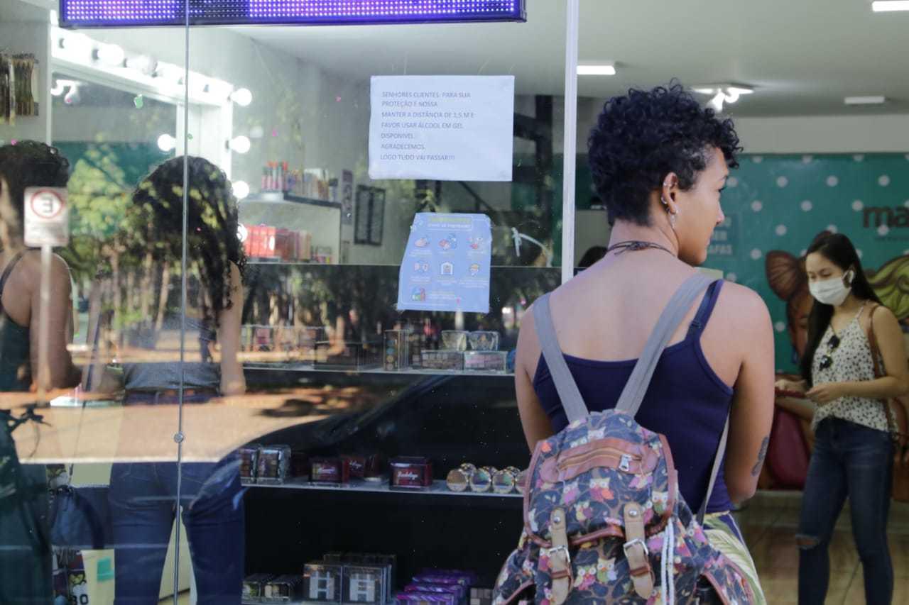 Cliente sem máscara espera para entrar em loja de maquiagem em Campo Grande (Foto: Kisie Ainoã)