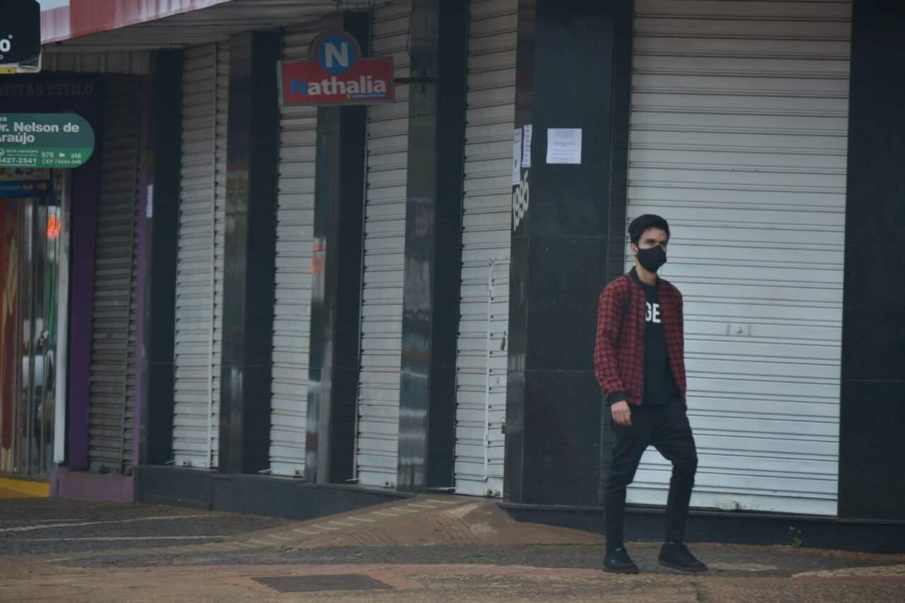 Douradense passa por lojas fechadas na Avenida Marcelino Pires (Foto: Eliel Oliveira)