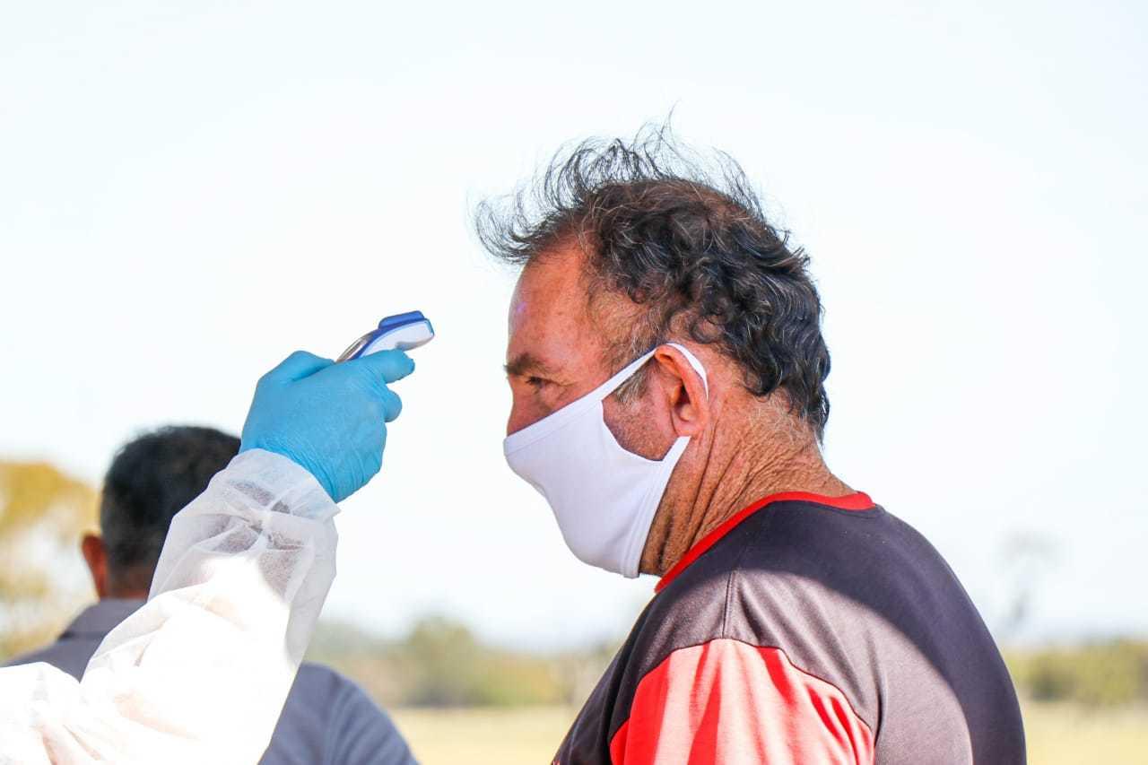Agente de saúde medindo a temperatura de homem. (Foto: Henrique Kawaminami)
