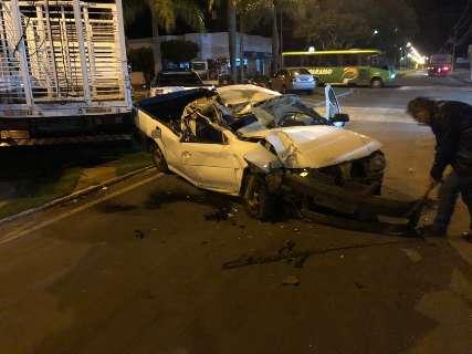 Carro fica destruído após bater em caminhão estacionado