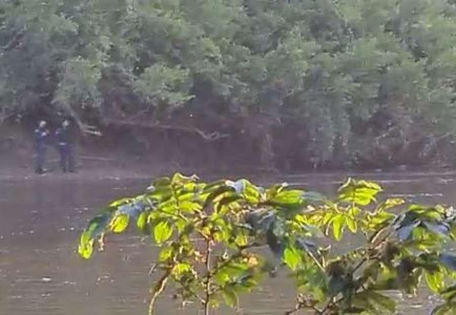 Policiais, na margem do rio, aguardam o suspeito ser resgatado (Foto: Divulgação)