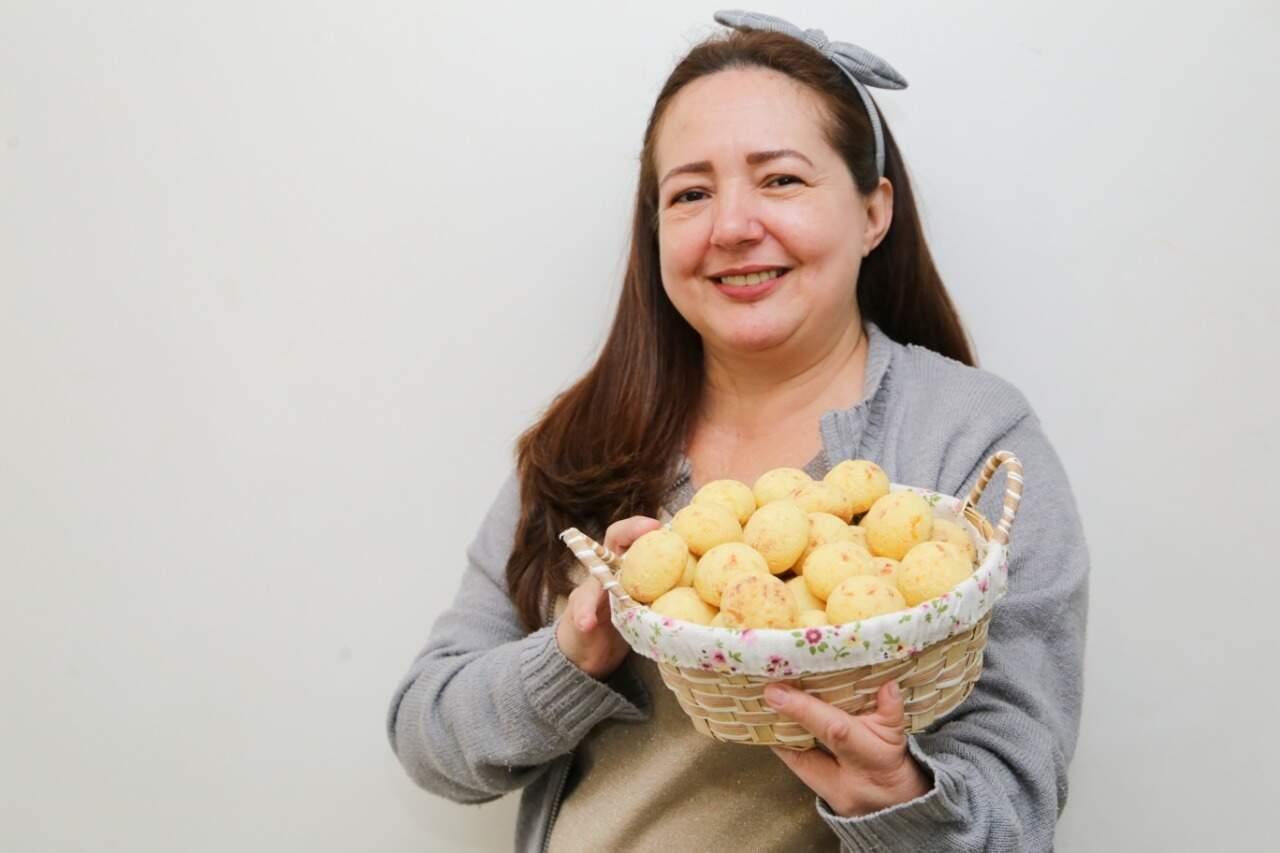 Ângela Aparecida Mendonça segurando uma cesta cheia de pão de queijo. (Foto: Kísie Ainoã)