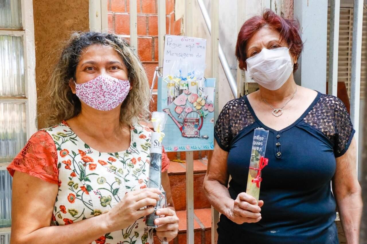 Na frente do portão, Alaíde Ferreia Prates (à esquerda) e Mercedes Prates Kobayashi seguram às revistas que também estão disponíveis. (Foto: Henrique Kawaminami)