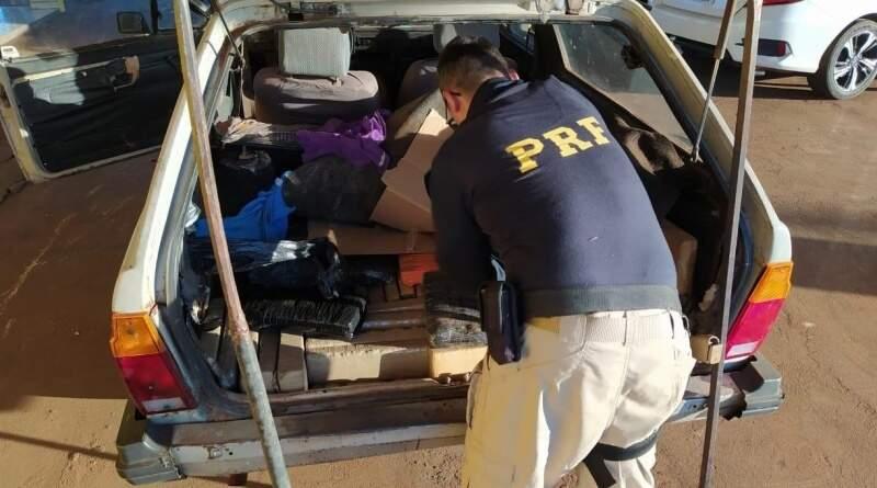 Policial retirando os tabletes de maconha do porta-malas do veículo. (Foto: PRF)