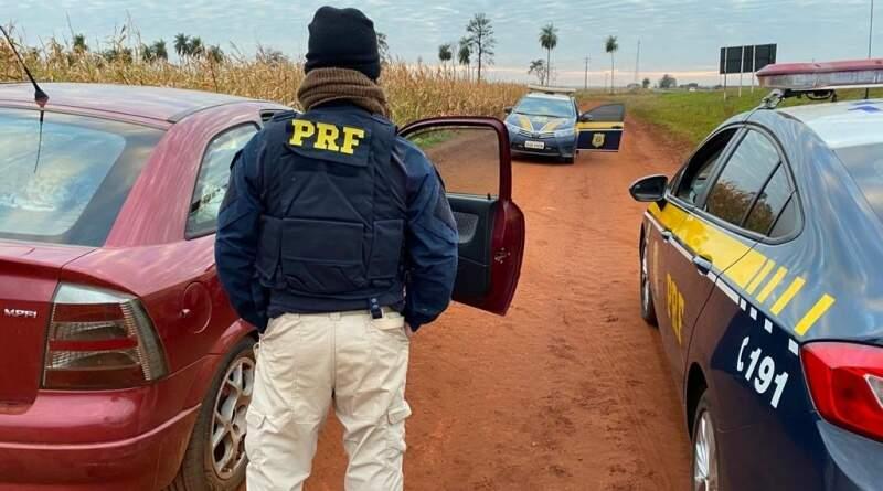 Policial ao lado do Astra onde foram encontradas as drogas. (Foto: PRF)