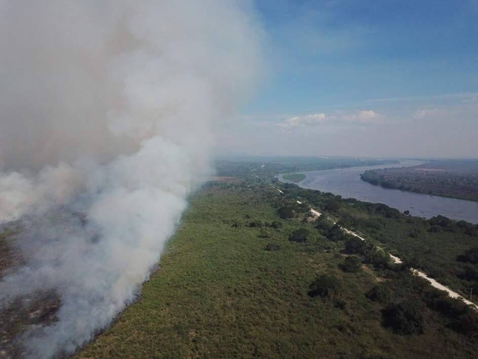 O Pantanal, metade fumaça, metade Rio Paraguai e dividido pela vegetação em horizonte sem indicativo de chuva (Foto: Thainan Bornato)