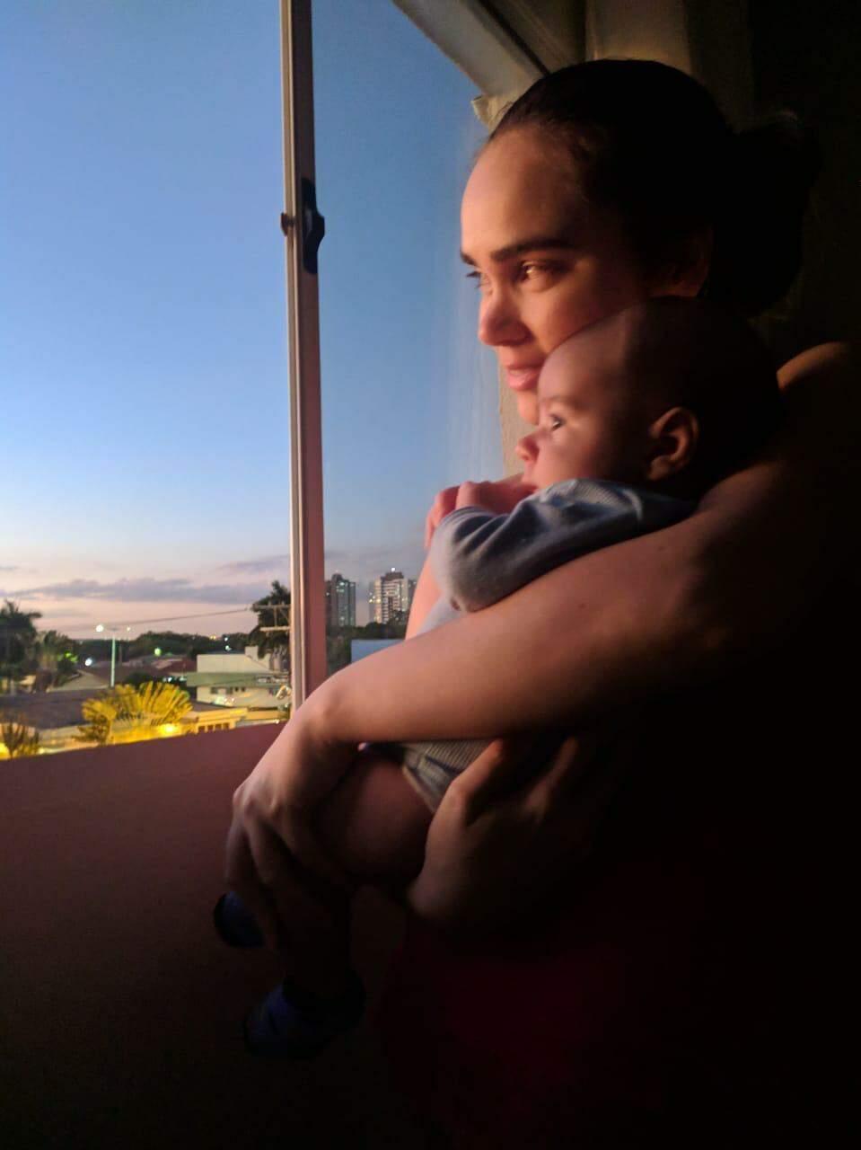 Aline Herrero e o filho Otto olhando a cidade pela janela. (Foto: Arquivo pessoal)