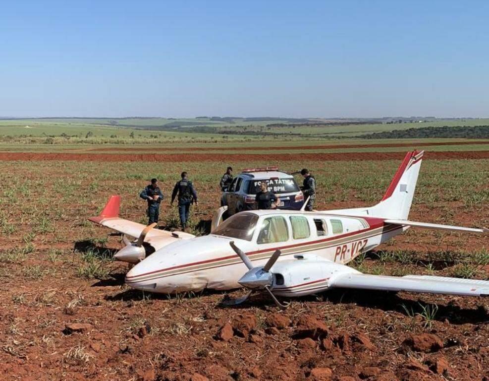 Policiais militares ao lado do avião abandonado em lavoura de cana, em Ivinhema (Foto: Divulgação)