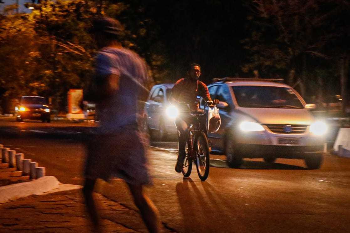 Homem correndo, clista passando e carros circulando por trecho do Parque dos Poderes, no período da noite (Foto: Henrique Kawaminami)