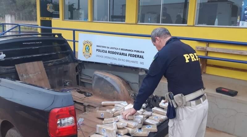Policial retirando os tabletes de drogas do fundo falso do veículo. (Foto: PRF)