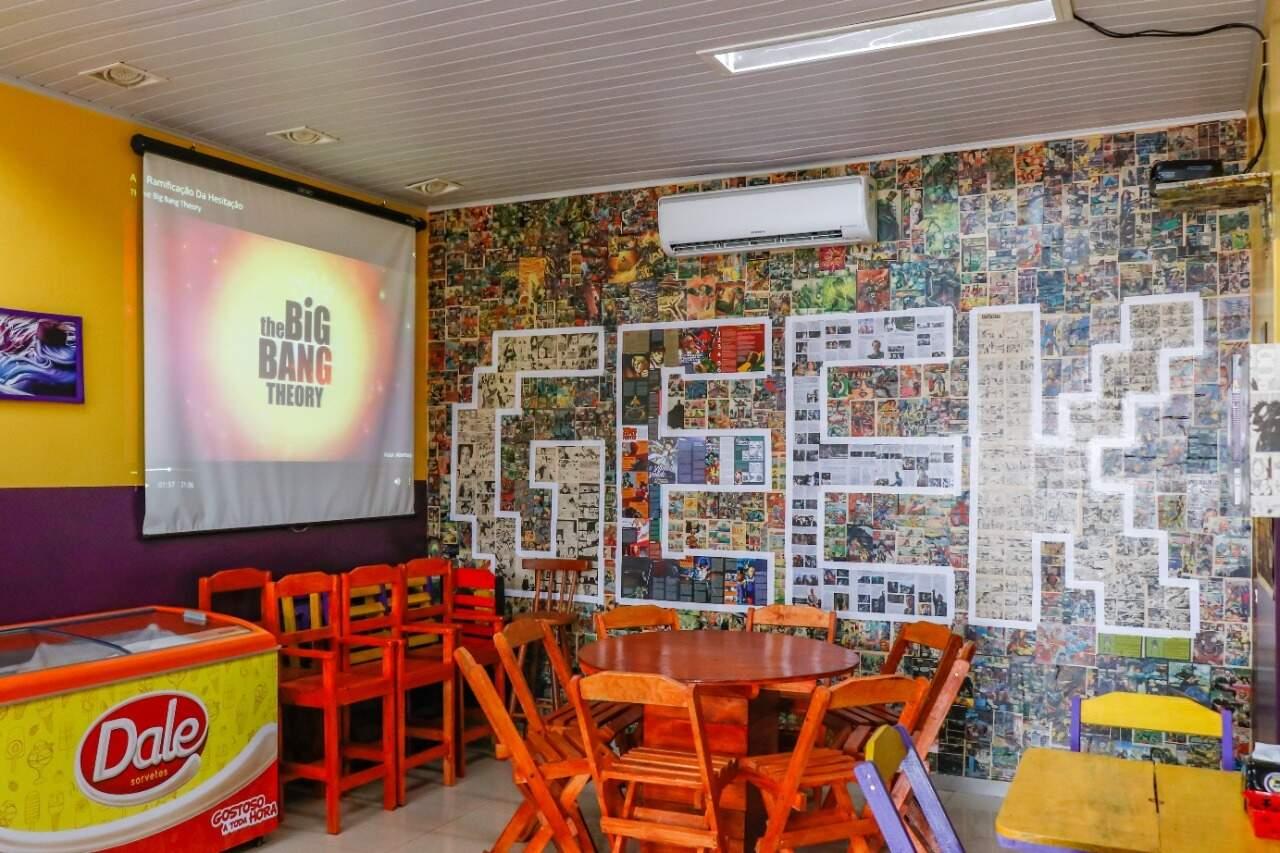 Nas paredes, telão para exibir filmes e exposição de gibis colada para decorar o ambiente. (Foto: Henrique Kawaminami)