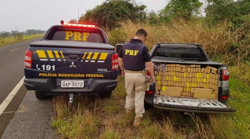Policia ao lado do veículo que estava carregado com os tabletes de maconha. (Foto: PRF)