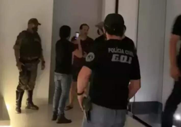 Aloysio, ao fundo de bermuda e chinelo, durante abordagem de policiais (Foto: Reprodução)