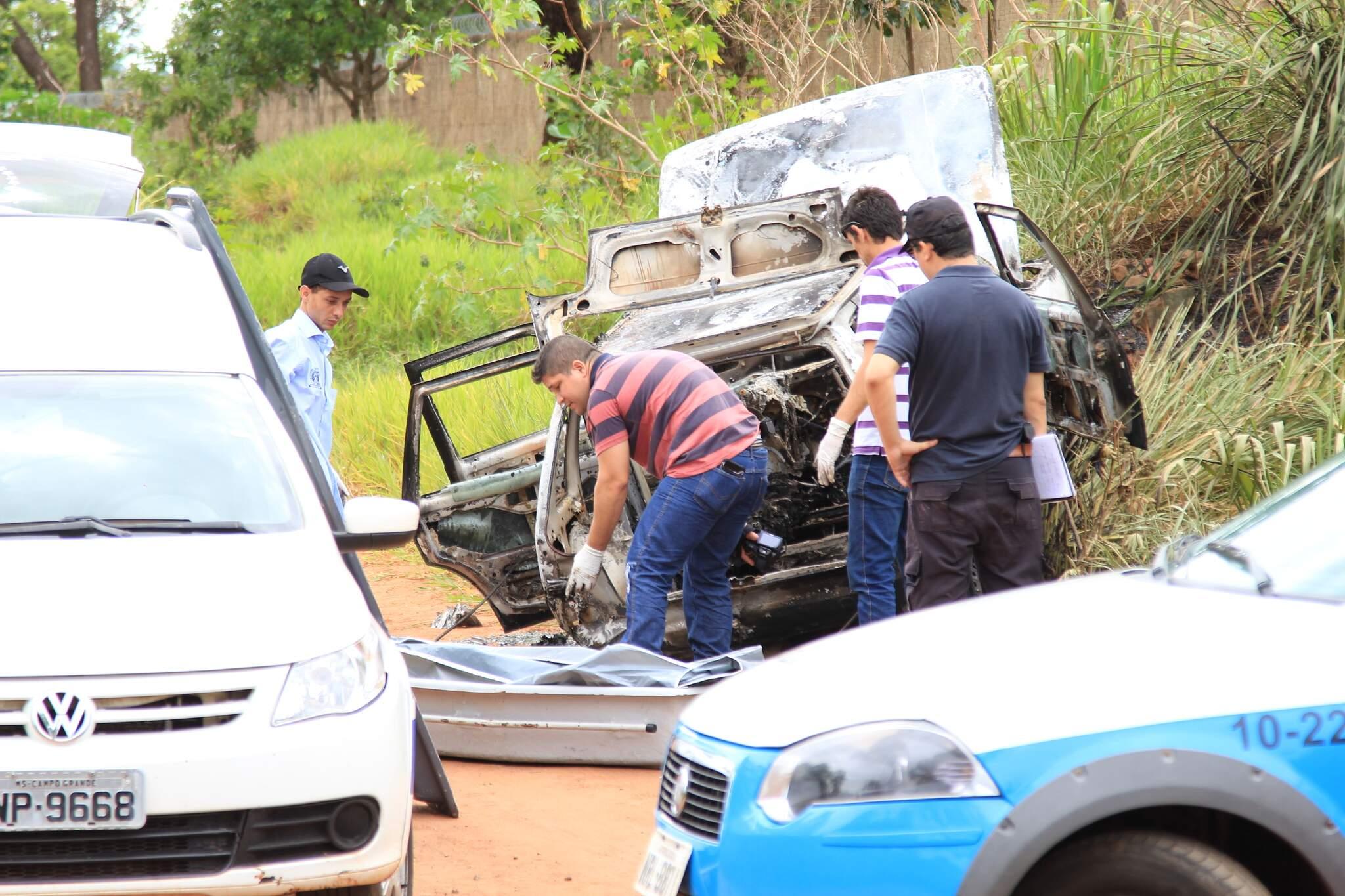 Corpo de vítima executada por acusado que teve juri adiado, sendo retirado de carro incendiado. (Foto: Arquivo)