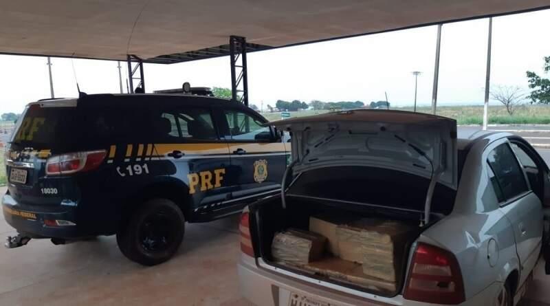 Viatura da PRF ao lado do veículo onde foi encontrada a droga. (Foto: PRF)