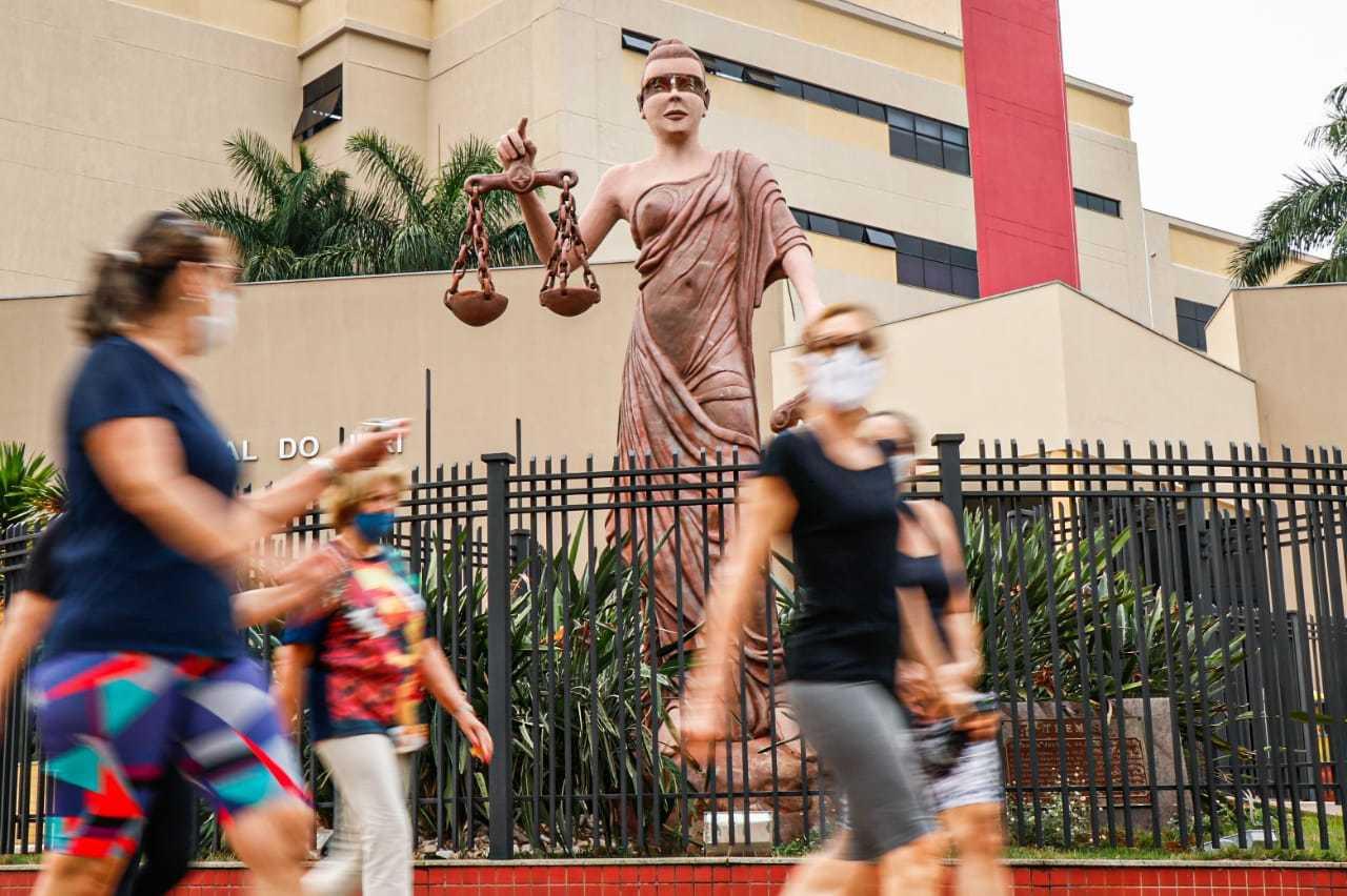 Pedestres passam em frente à estátua da deusa Thêmis, no Fórum de Campo Grande, cuja venda nos olhos caiu e será recolocada. (Foto: Henirque Kawaminami)