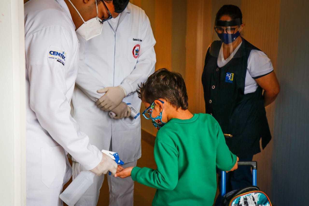 João Pedro chegando à escola, limpando as mãozinhas com álcool em gel. (Foto: Henrique Kawaminami)