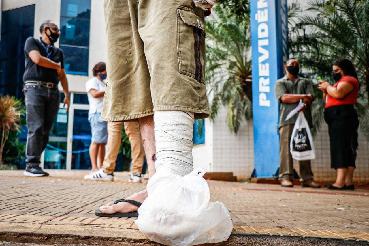 Homem, com o pé quebrado, aguarda por atendimento em agência de Campo Grande (Foto: Henrique Kawaminami)