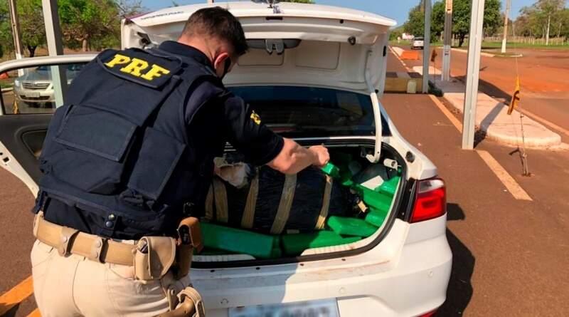Policial rodoviário federal retirando tabletes de maconha de porta-molas de veículo apreendido (Foto: Divulgação/PRF)