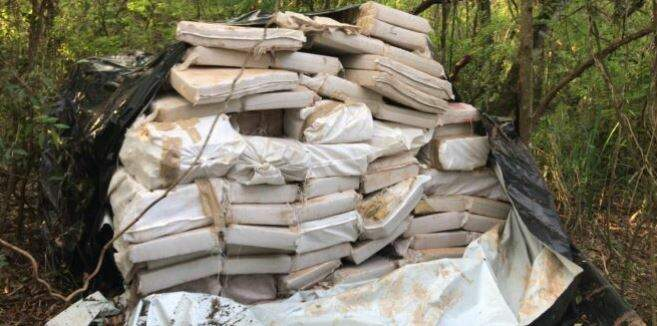 Tabletes de maconha estavam cobertos por uma lona em chácara. (Foto: Ponta Porã News)