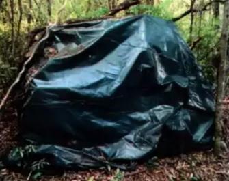 Lona preta cobria carga de maconha em chácara onde a polícia encontrou quarto com roupas e documentos de policial civil. (Foto: Reprodução de processo)