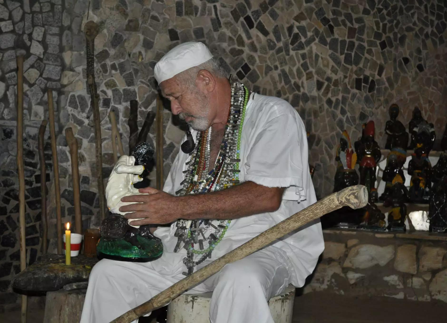Pai Marcílio dá benção na figura que simboliza Preto Velho, uma das várias linhagens de entidades na umbanda brasileira (Foto: Reprodução/Facebook)