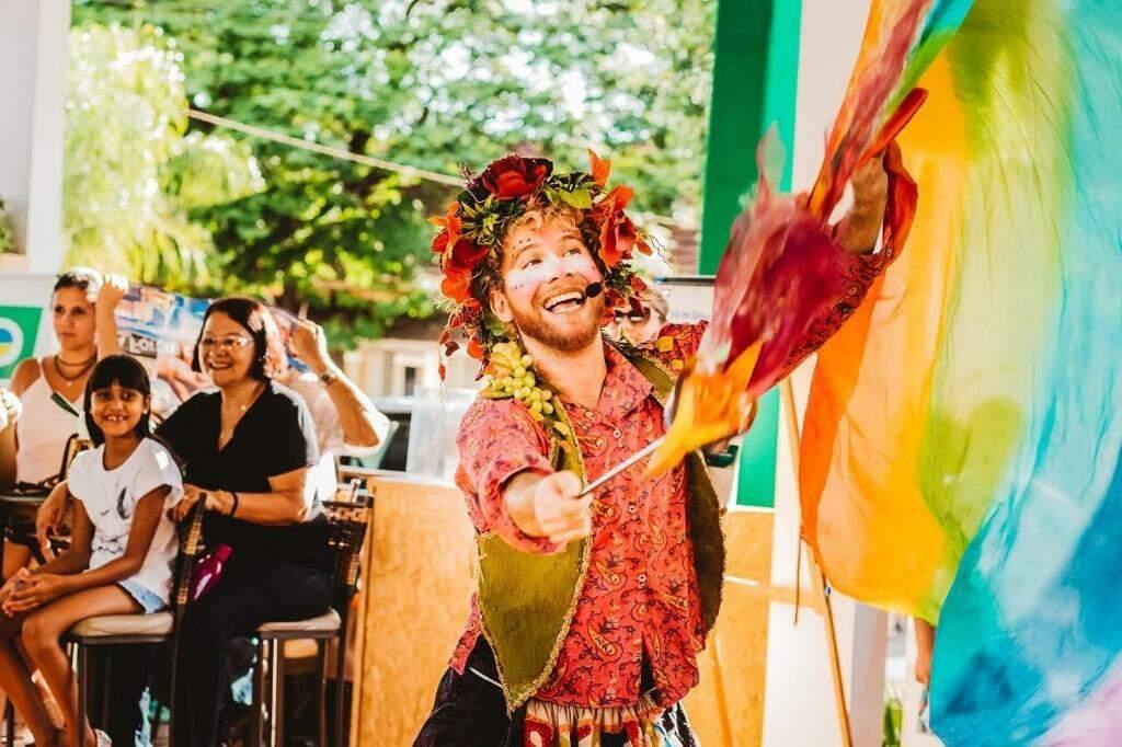 Criança sorri enquanto ator faz performance com tecidos coloridos (Foto: Arquivo Pessoal)