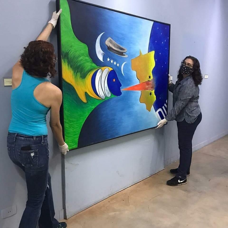 Equipe retira pintura para ser guardada em local seguro (Foto: Reprodução/Facebook)
