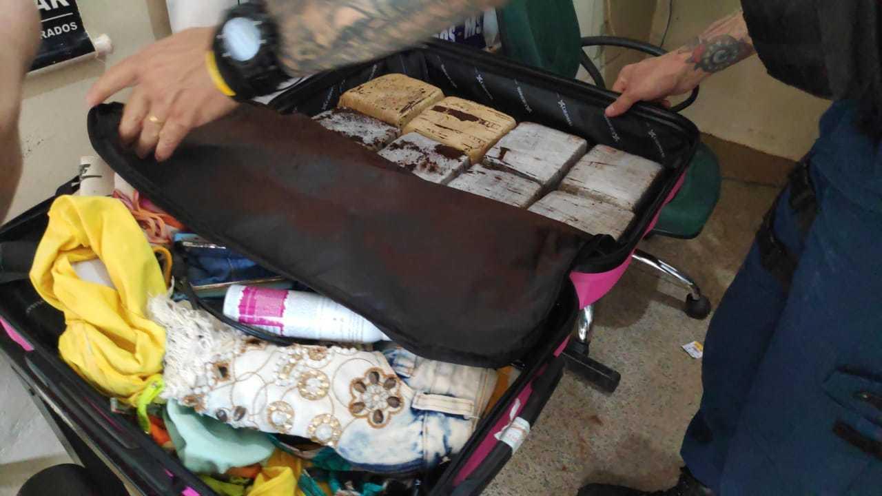Policial retira tabletes de maconha de mala encontrada com modelo de 17 anos (Foto: Adilson Domingos)