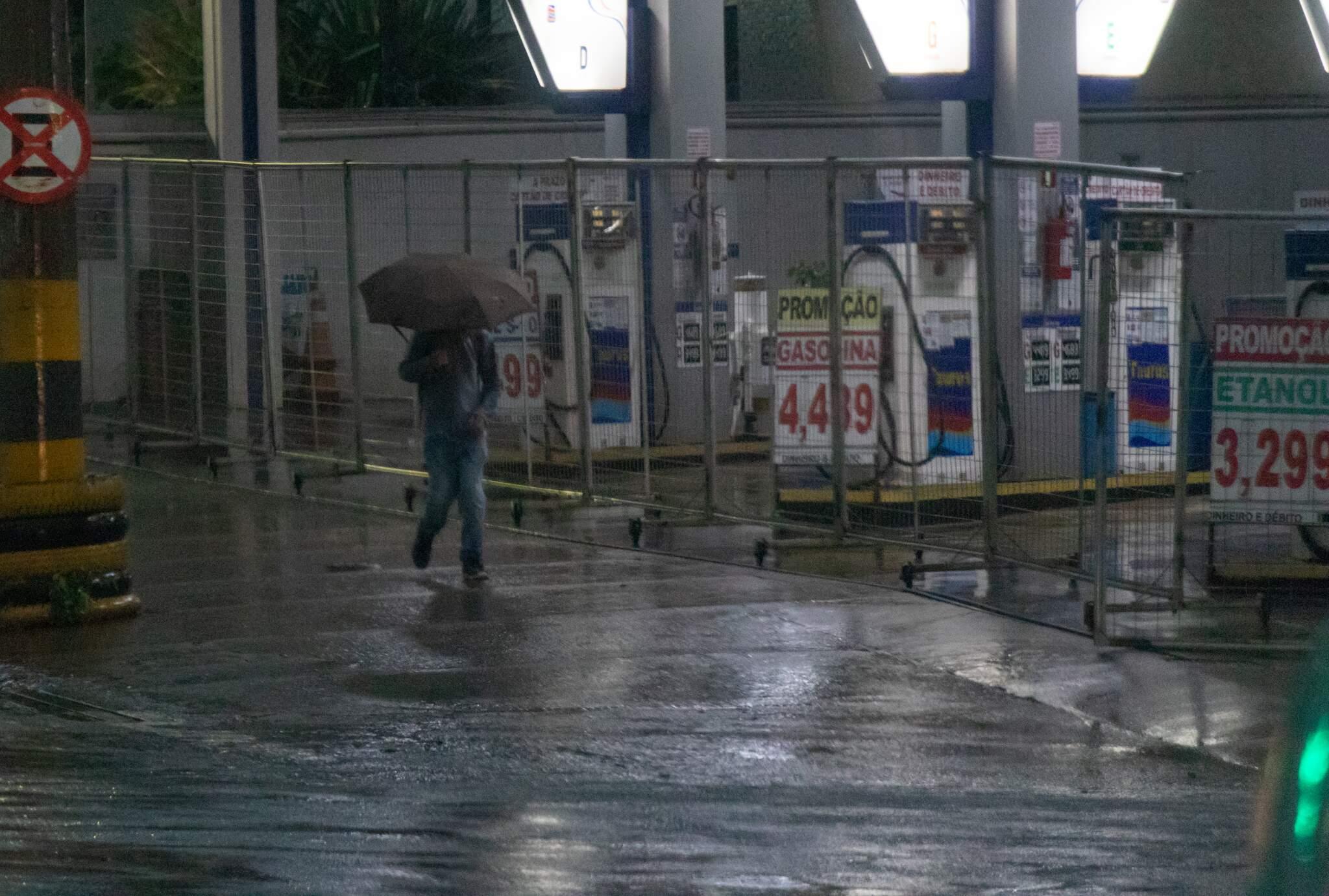 Pedestre caminhando em meio a enxurrada na região central de Campo Grande, nesta manhã (Foto: Henrique Kawaminami)