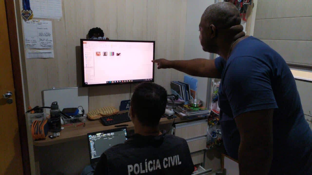 Policiais avaliam material apreendido com suspeitos de armazenar material pornográfico infanto-juvenil. (Foto: Divulgação)
