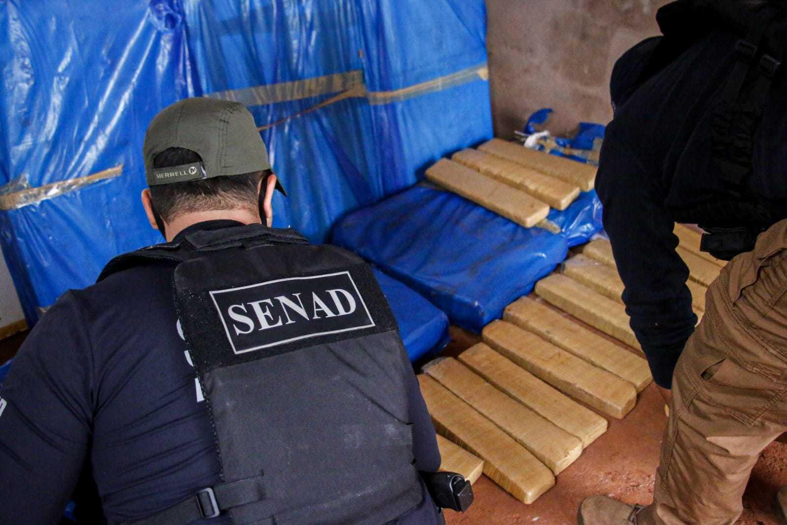 Agentes da Senad no cômodo onde estavam os tabletes de maconha (Foto: Divulgação)