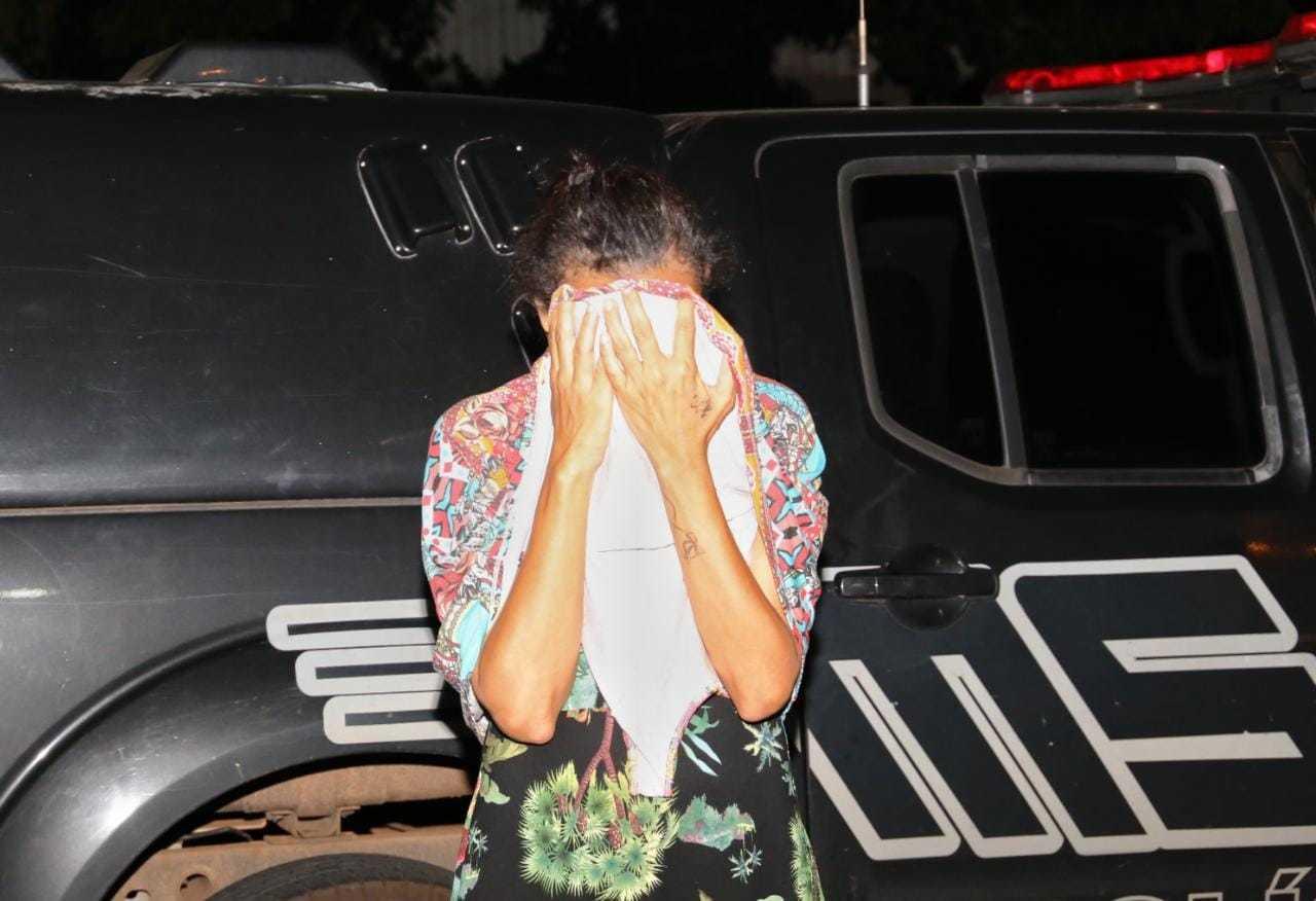 Clarice com o rosto coberto ao chegar à delegacia (Foto: Paulo Francis)